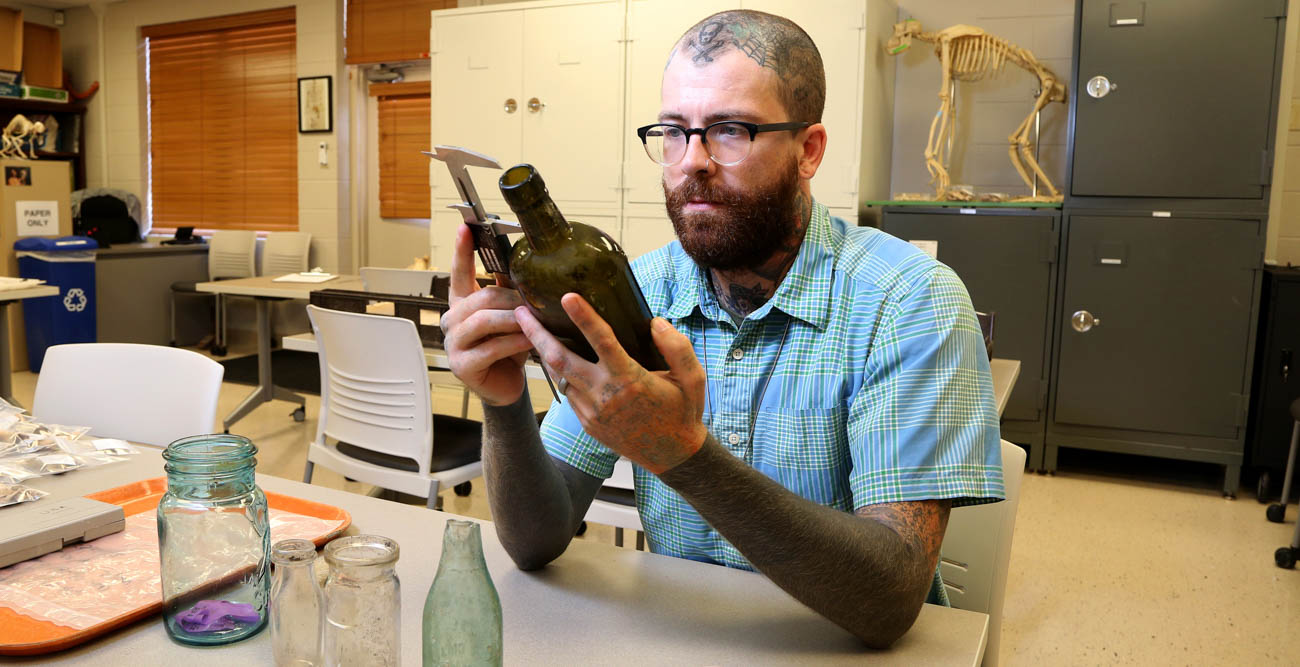 Dusty Norris, a graduate of the University of South Alabama's anthropology program, is using an archaeology tool to record information about one of the artifacts found at the sites of the shotgun houses in areas of downtown Mobile. This preliminary work is being done as plans for the Mobile River Bridge and Bayway project moves forward.