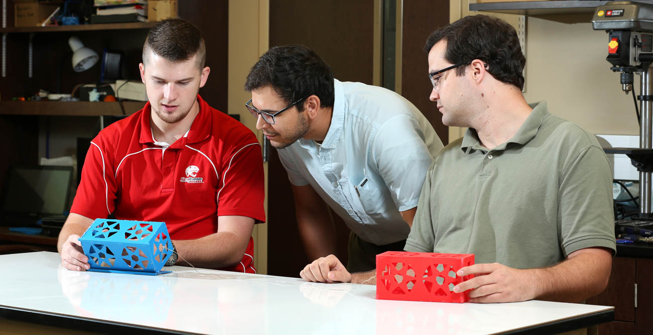 Graduate students Harrison White and Matthew Simmons flank Dr. Carlos Montalvo as they discuss the tradeoff from having two or more miniature satellites, called CubeSats, connected via a tether from an E-Sail. More CubeSats means more tethers and more thrust, but also more chances of tangling.