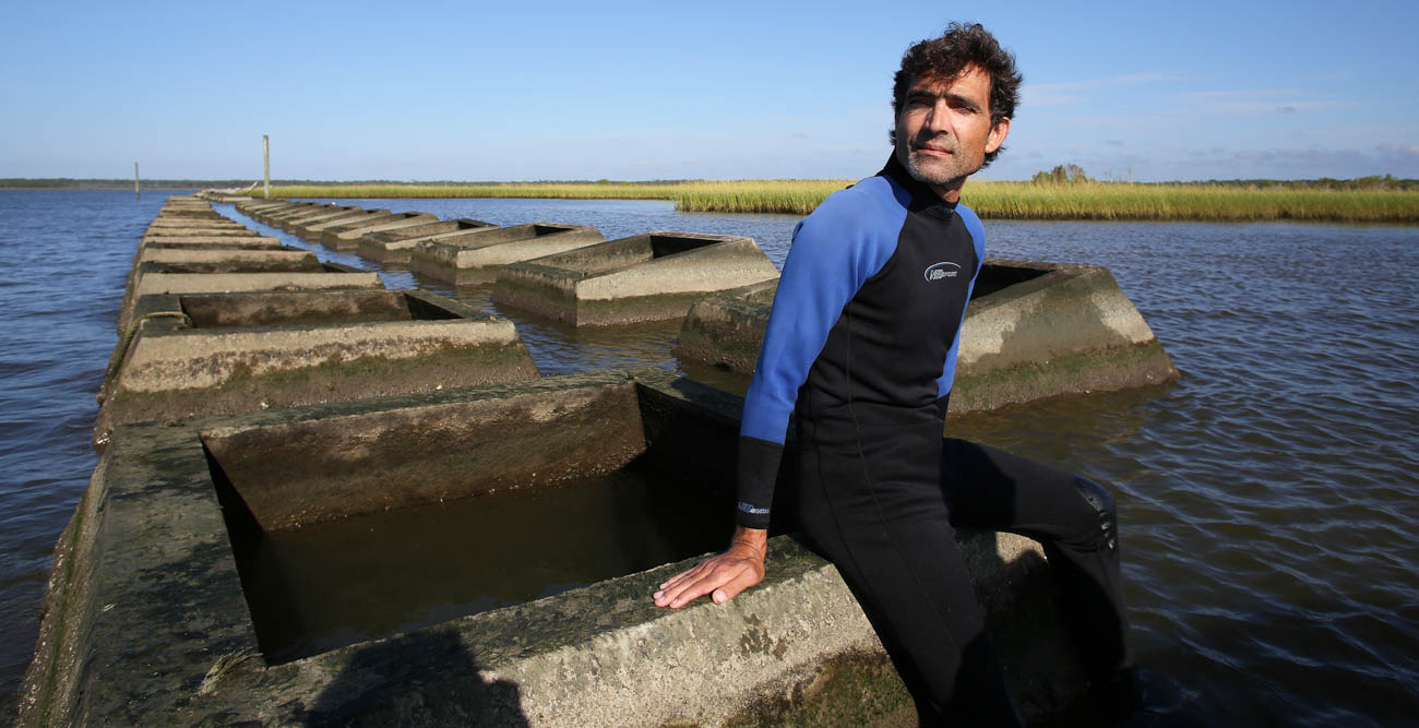 Dr. Just Cebrian, a marine science professor at the University of South Alabama, sits atop a mile-long row of concrete blocks placed between Portersville Bay and Little Bay to defend against erosion. The project was initiated after a berm was destroyed by Hurricane Katrina in 2006. The result: Sea grass that was planted has flourished, offering protection against hurricanes and for seafood and wildlife habitats.