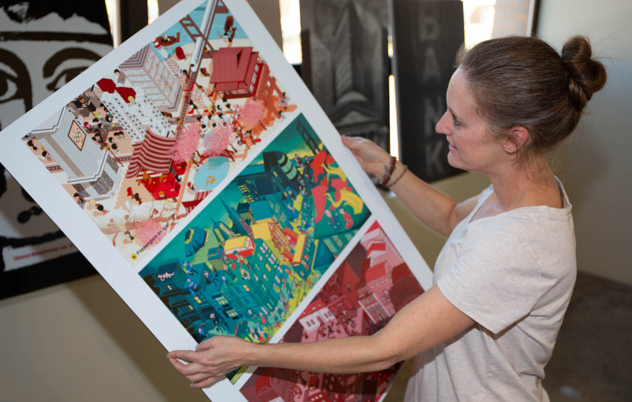 Graduate student Yvonne LeBrun prepares to hang the art for the Cross Connections 2018 International Exhibit of Design & Illustration.The exhibit runs through Oct. 31.
