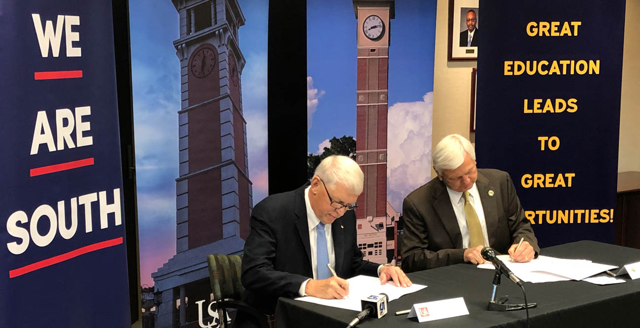 University of South Alabama President Tony Waldrop, left, and Pensacola State College President Edward Meadows sign documents officially joining the two institutions as part of South's