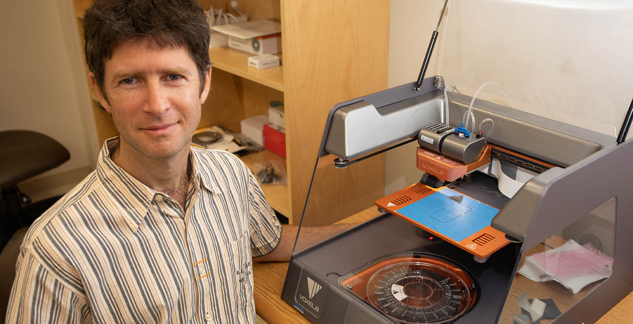 Dr. Mark Yampolskiy, assistant professor in the School of Computing pictured with 3D printing device