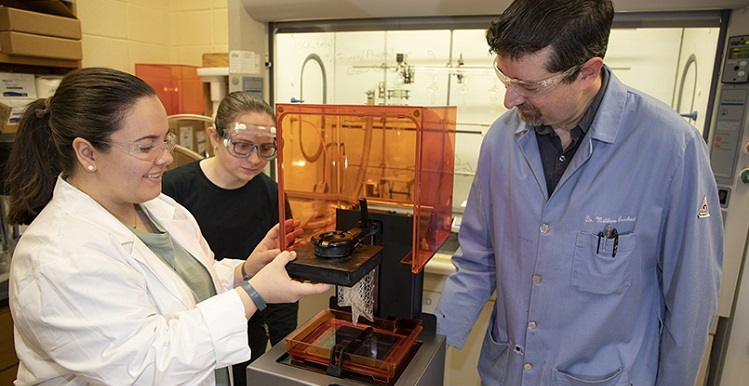 Senior chemistry students Madison McBroom, left, of Huntsville and Amanda Tanner of Cantonment, Fla., listen as Dr. William Richert talks about their research with ionic liquids in the field of 3D printing.