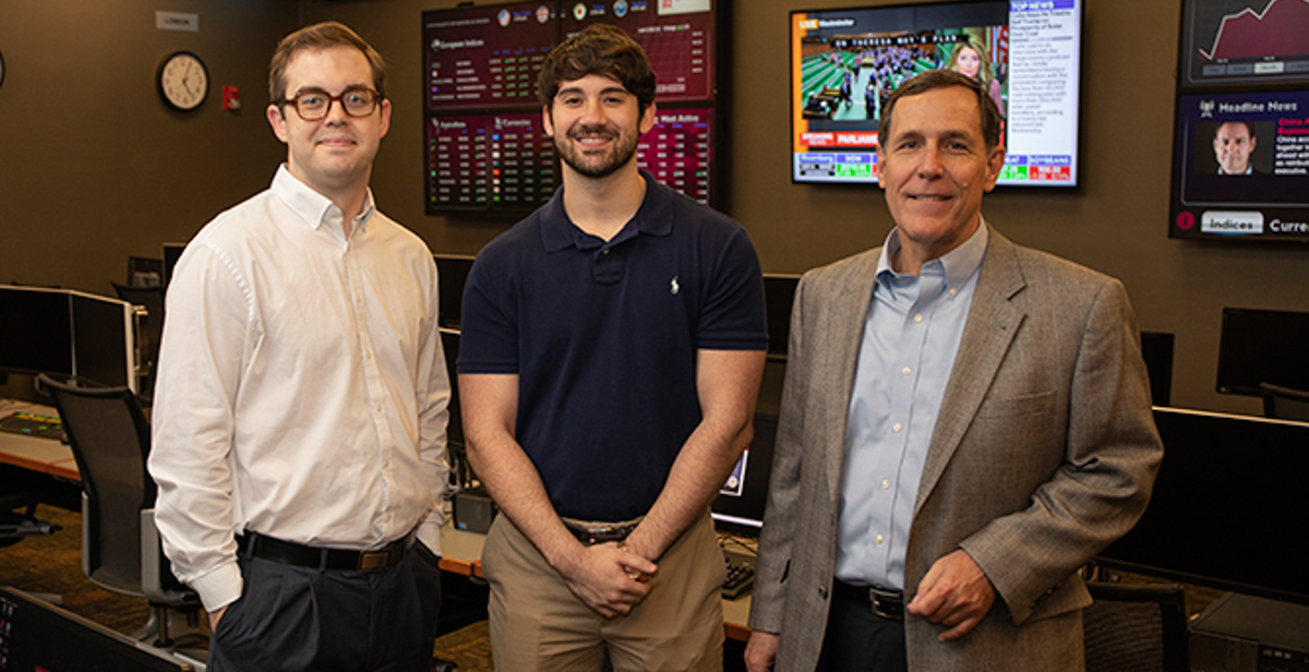 Jacob Corbett, left, and Taylor Shepherd, center, are two of the six Mitchell College of Business students on a team that won the 2018 University Portfolio Challenge. Dr. Reid Cummings, director of USA's Center for Real Estate and Economic Development, and the team's mentor, right, taught the Finance 446 class each of the students took.