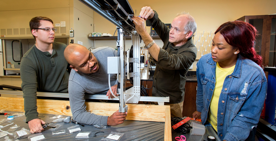 Electrical engineering senior Zack Peavy of Citronelle, mechanical engineering senior Kiante Evers of Gulfport, Miss., and computer engineering senior Ariel Pickett of Montgomery are adjusting the vertical travel distance of the robot head for a space station that will be used to grow crops in space. Assisting the students is Dr. Sam Russ, associate professor of electrical and computer engineering at the University of South Alabama.