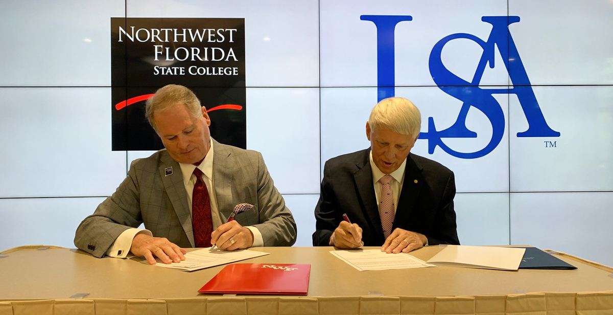 Dr. Devin Stephenson, left, Northwest Florida State College president, and Dr. Tony Waldrop, University of South Alabama president, sign an agreement that adds NWF State College to the list of Gulf Coast institutions that have joined South's Pathway USA program, increasing access to a four-year education for community college students.