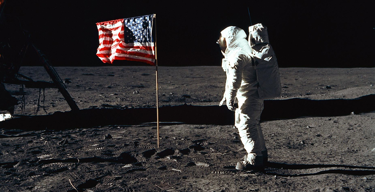 "Astronaut Edwin ""Buzz"" E. Aldrin Jr., lunar module pilot of the first lunar landing mission, poses for a photograph beside the deployed United States flag. NASA photo."