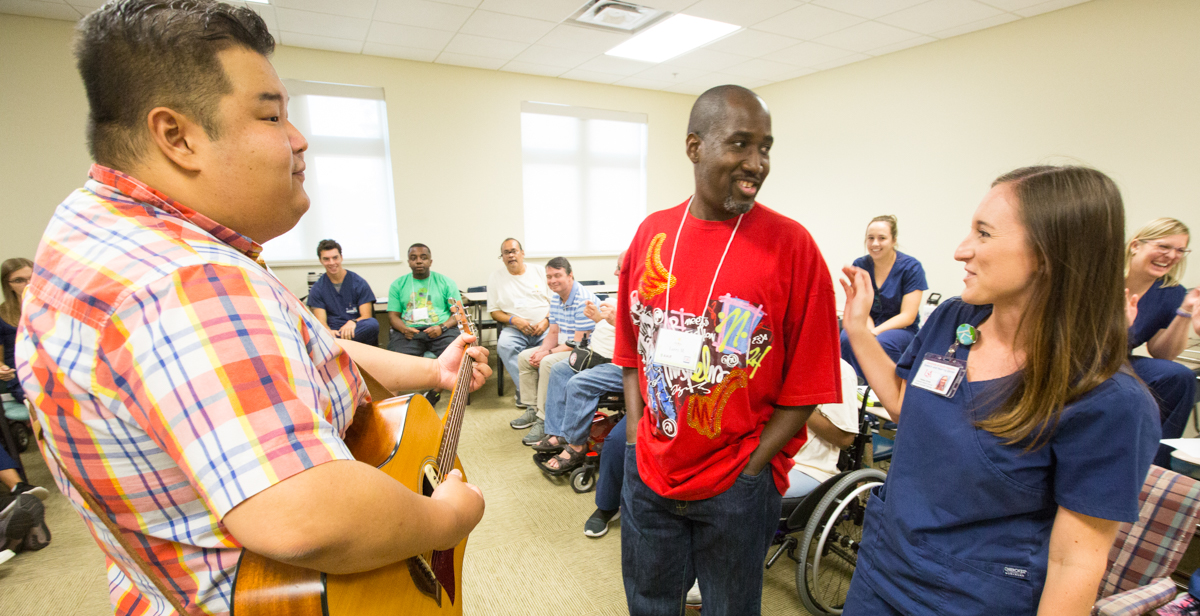 Kelsey Gross, University of South Alabama speech-language pathology graduate student, assists traumatic brain injury camp participant Larry Malone Jr., center, while music therapist Fred Ra leads Malone and other camp participants in creating a song using words suggested by the group. data-lightbox='featured'