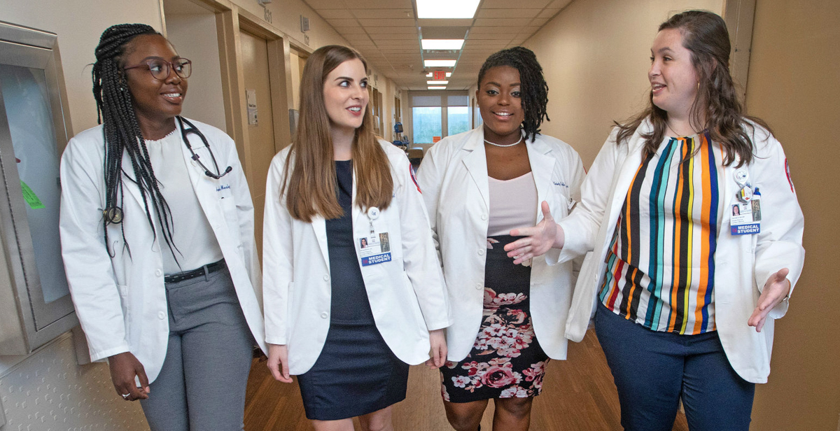 Angela Mosley-Johnson, Samantha Lee, Kimberly McWilliams and Hannah Brooks chat during a break in clinical rotations at USA Health University Hospital. The third-year students at the University of South Alabama College of Medicine have been awarded scholarships from Blue Cross and Blue Shield of Alabama as part of initiative to improve access to healthcare in underserved areas of the state.