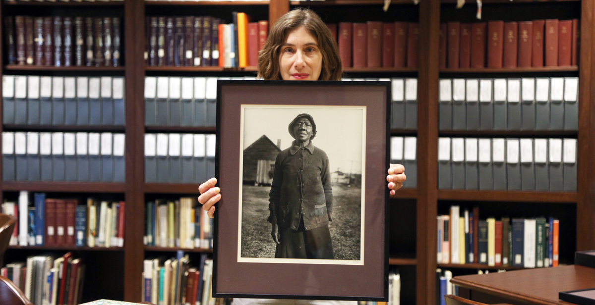 Deborah Gurt, archivist for the Doy Leale McCall Rare Book and Manuscript Library, holds one of the Eurdora Welty prints in the Iredale Collection donated to the University of South Alabama. The photo is one of a series taken by Welty as part of her job with the Works Project Administration during the Great Depression.