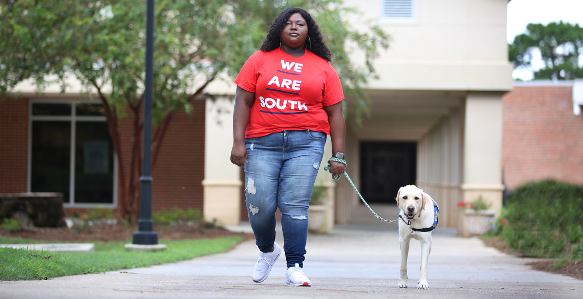 "Kearria Freed, a transfer student pursuing a degree in interdisciplinary studies, uses Darling, her 2-year-old Labrador/Golden Retriever service dog, to navigate life after she was critically wounded in a shooting four years ago. ""What I love most about Darling is that she doesn't judge me because of my disability. Instead, she gives me unconditional love and affection,"" Freed said. data-lightbox='featured'"