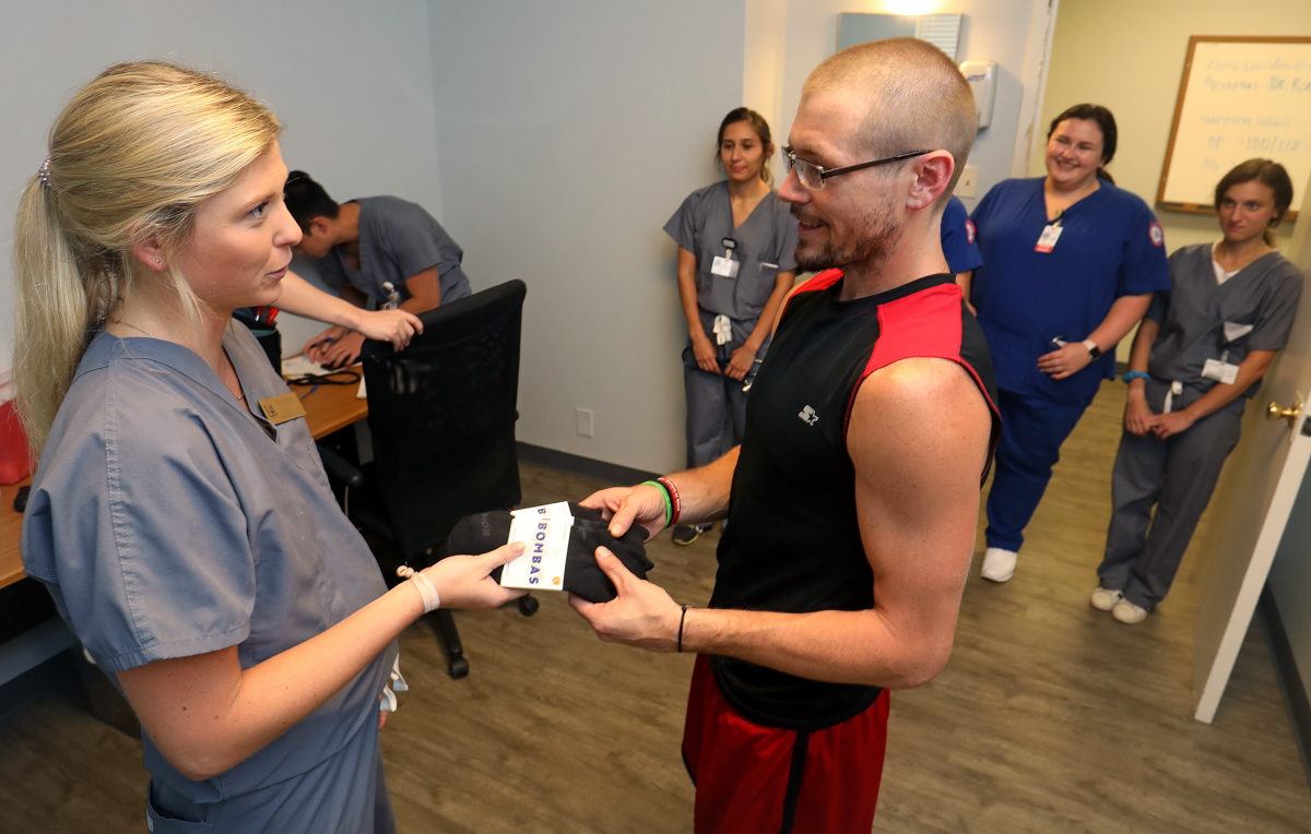 University of South Alabama College of Medicine medical student Corey Phillis gives a pair of socks to Paul Brown at the USA Student-Run Free Clinic.