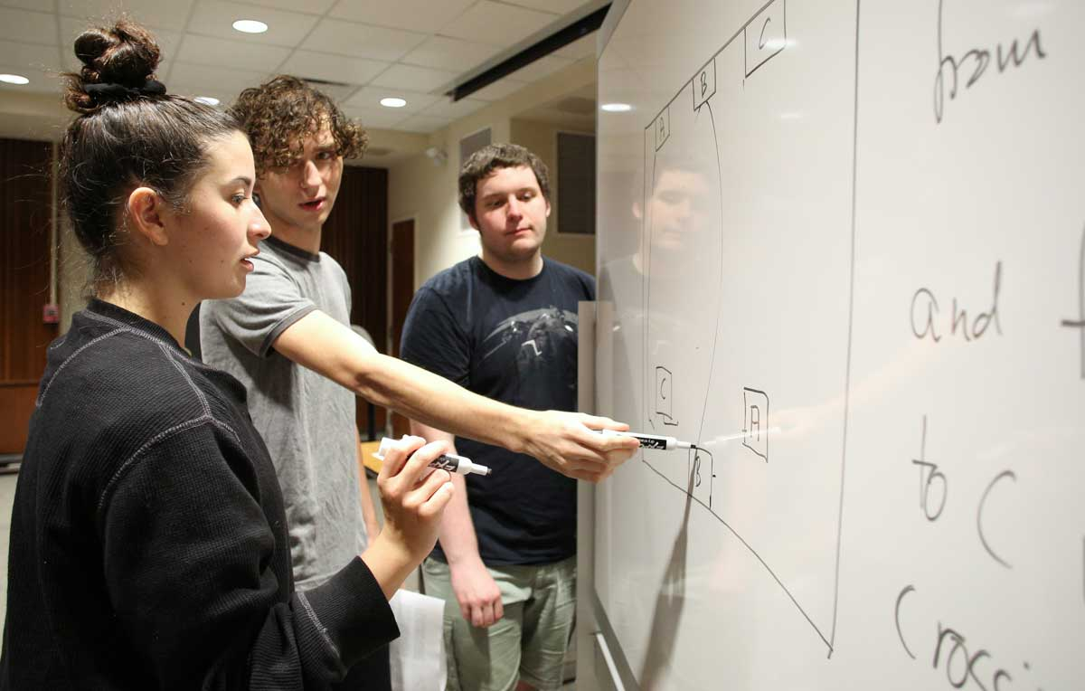 USA students John Pomerat, center, a sophomore computer science and mathematics major, along with Daniel Hodgins, a freshman engineering major, show Murphy High School student Mollee Bearden how to problem solve during a recent Math Circle session.