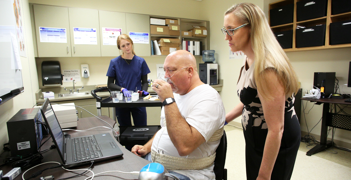Dr. Kendrea Garand, an assistant professor of speech pathology in the Pat Capps Covey College of Allied Health Professions, works with a volunteer control subject to collect data on swallowing against data collected from an ALS patient. The goal of her research is to improve treatment options for those who suffer from dysphagia.