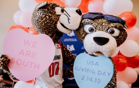 Southpaw and Pawla holding Giving Day Hearts