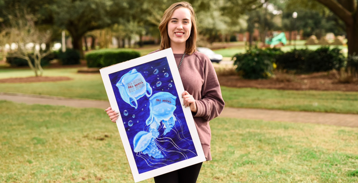 Grace Richardson, a University of South Alabama freshman from Hoover, holds a painting that was part of her Project Aquarius campaign. She earned the Girl Scouts' Gold Award as a result of her work.