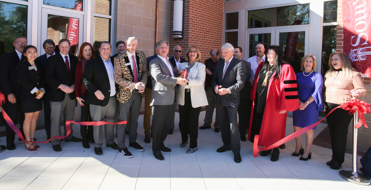 Julian and Kim MacQeen, center, join South alumni and supporters to cut the ribbon on the MacQueen Alumni Center. The 15,000-square foot-facility is in the center of campus, across from Moulton Tower and Alumni Plaza.