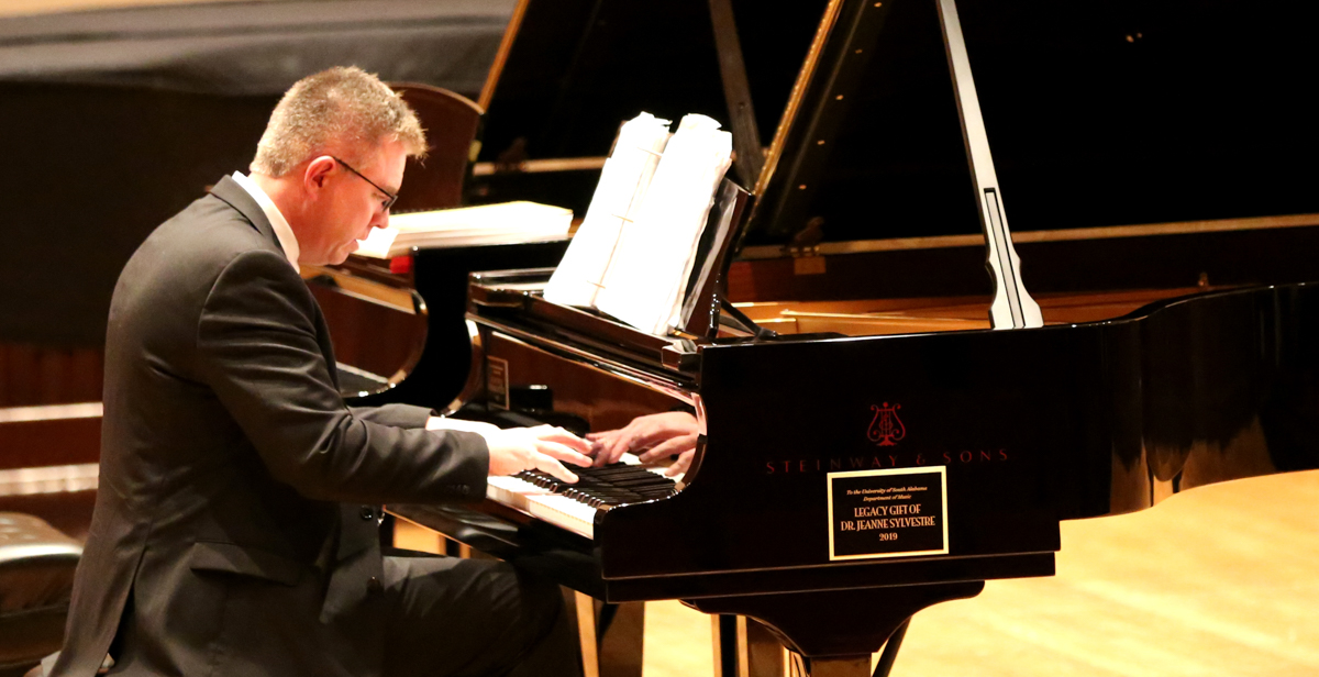 Dr. Robert Holm, professor of music at the University of South Alabama, plays on a Steinway recently donated to the department of music through a legacy gift by Dr. Jeanne Sylvestre, an emeritus professor of accounting.