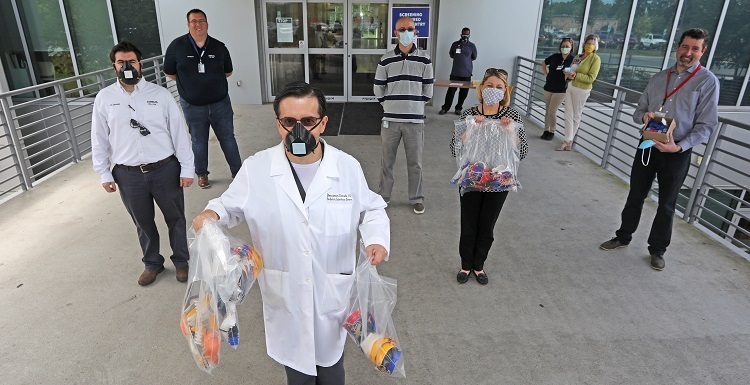 Dr. Benjamin Estrada, front, an infectious disease specialist at USA Health, accepted a delivery Friday of medical masks and tension-relief bands made by Airbus engineers and faculty at the University of South Alabama.