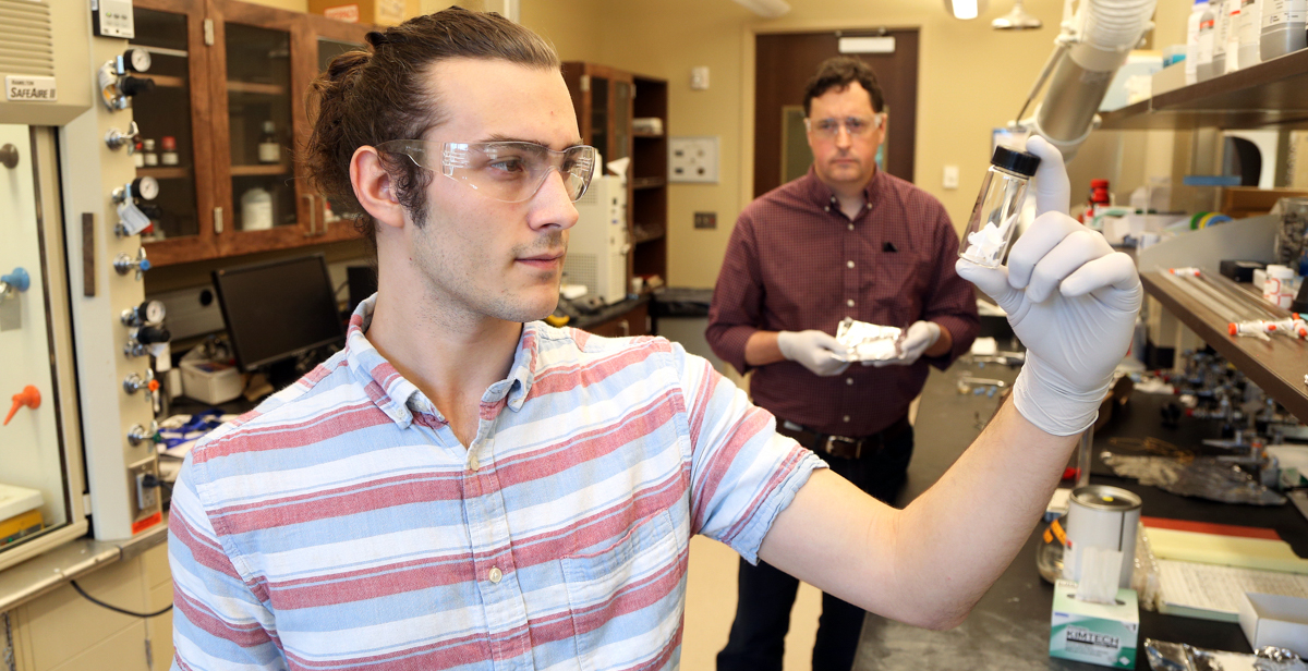Joe Milter, who graduated in May from the University of South Alabama, works with Dr. Kevin West, background, professor of chemical engineering, in a College of Engineering lab during spring semester. Milter is one of the students who has worked on an antimicrobial fiber research project, collaborated on by West and Drs. Grant Glover, associate professor of chemical engineering, and Terry Ravine, associate professor of biomedical sciences.