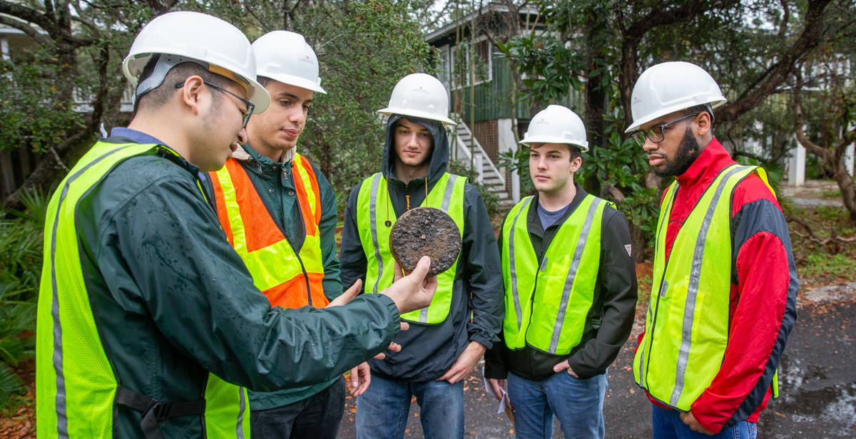 University of South Alabama engineering students examine an asphalt pavement core sample held by Dr. Shenghua Wu, assistant professor of civil engineering/pavement engineering. The sample was removed from a road made from 100 percent reclaimed asphalt pavement, which is the focus of research by Wu and the students.