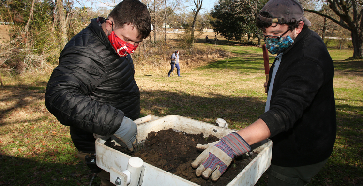 From L-R; Will Marriott, staff archaeologist, USA Center for Archaeological Studies, and Jeremy Pruitt, field technician, USA Center for Archaeological Studies sift through soil collected during a cultural resource survey in the Africatown community of Mobile.