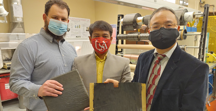 Researchers from the William B. Burnsed Jr. Mechanical, Aerospace, and Biomedical Engineering Department. From L-R; Michael Johnson, MS student and Graduate Research Assistant, Nazim Uddin, MS student and Graduate Research Assistant, Prof. Kuang-Ting Hsiao display a unidirectional ZT-CFRP Prepreg sample produced in Hsiao's lab and a ZT-CFRP Composite Panel manufactured from stacks of ZT-CFRP prepregs.