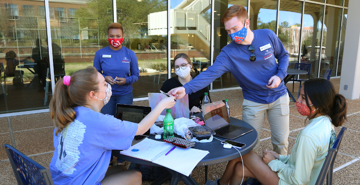 Grant Skinner and Sarai Garraway, both juniors and South Strong Ambassadors at the University of South Alabama, meet with fellow students recently outside the Student Center to talk about the importance of following precautions to keep people safe from COVID-19.