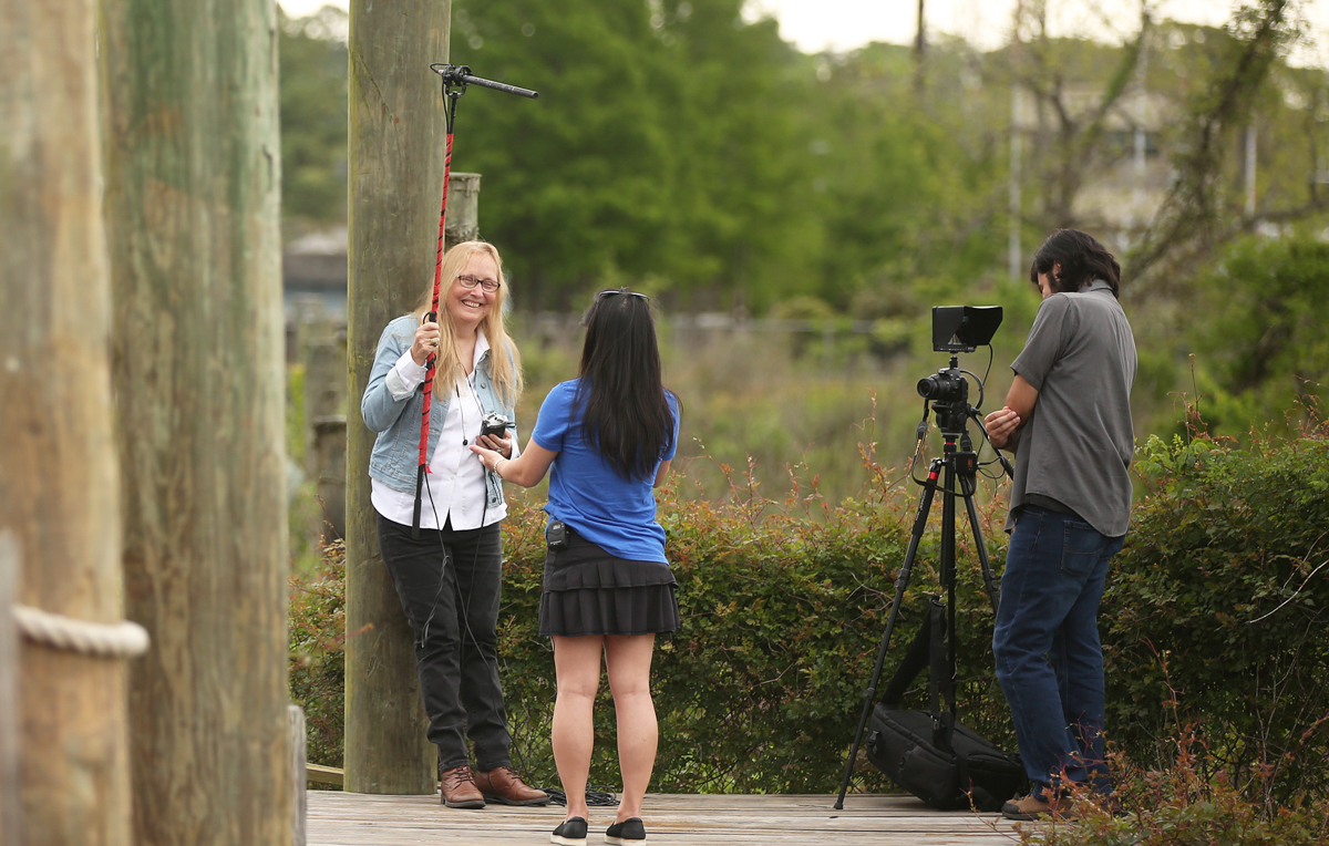 Dr. Lorraine Ahearn, an assistant professor of multimedia journalism at the University of South Alabama, holds a boom microphone for her interview with a Bayou Le Batre resident who moved there from Vietnam as a child. Ahearn is producing a documentary about the Vietnamese fishing community on the Alabama Gulf Coast. The videographer on many of her interviews is Francisco Cordova, right, a December graduate from the digital cinema and television program.