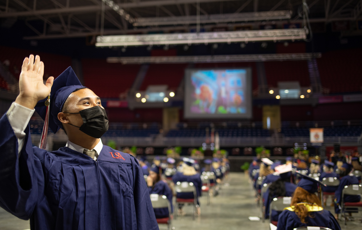 A 2021 College of Nursing graduate waves as he walks during spring commencement ceremony.