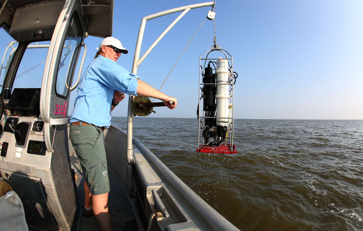 Dr. John Lehrter, associate professor of marine science, pulls up a submersible instrument used to measure the water's temperature and oxygen and salinity levels.