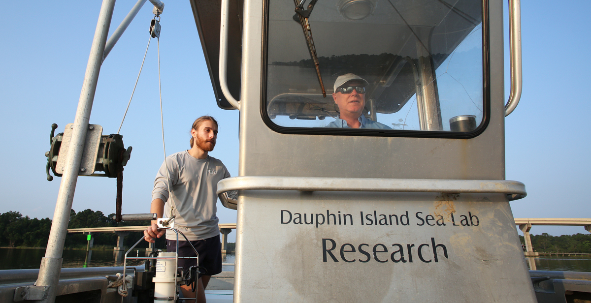 Dr. John Lehrter, associate professor of marine science, pilots a boat through Mobile Bay, where he and graduate Chris Mikolaitis took water samples to measure the health of its marine ecosystem.