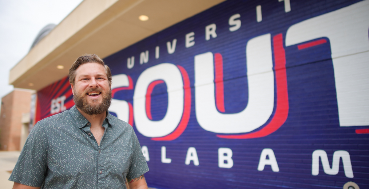 Muralist and University of South Alabama graduate Andy Scott's latest work is on the side of the USA Student Center — a bright mural in Pantone 281 and 193.