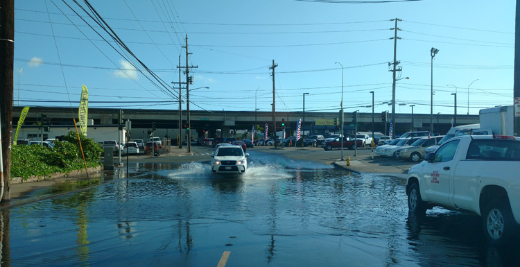 """Saltwater flooding in a busy intersection in Oahu, HI is the result of sea level rise causing higher tides that back up the stormwater system. This type of flooding is known as """"high tide flooding,"""" """"sunny day flooding,"""" or """"nuisance flooding."""" It's an example of how sea-level rise is affecting everyday life in coastal regions."""
