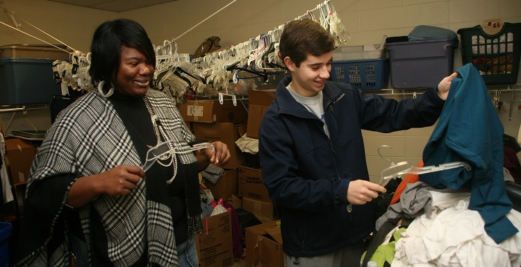 Bobbi Vaughn Kidd, food nutritionist at Dumas Wesley Community Center sorts clothing items with USA student Reed Morler, a pre-physical therapy major and presidential scholar.