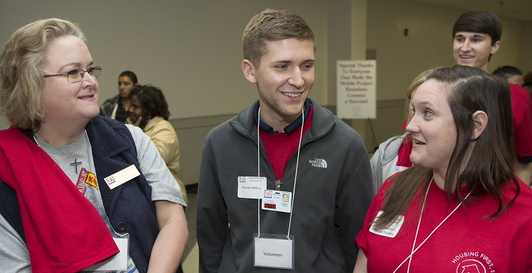 University faculty, staff and students assisted at the Project Homeless Connect event at The Grounds. Talking with two USA student volunteers is Karen Peterson, director of USA's Center for Academic Service-Learning and Civic Engagement.