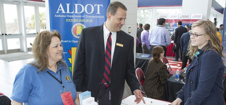 student speaking with two ALDOT representatives at career fair