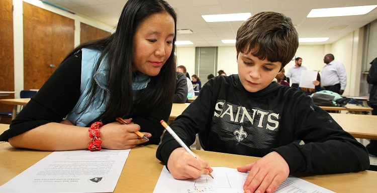 Min Zhu, a University of South Alabama student pursuing her master's degree in math education, helps 8th-grader Ian Robertson of Mobile problem solve during a weekly Math Circle session at South.