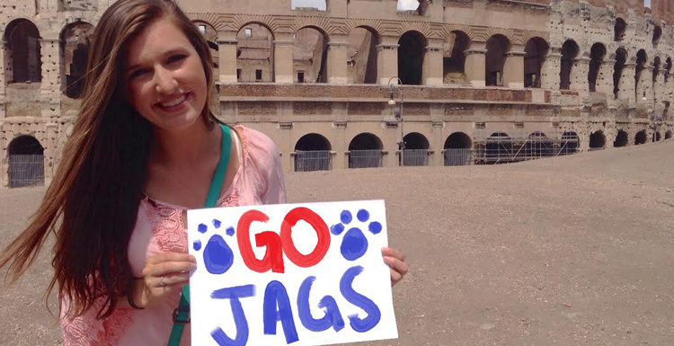 Student holding Go Jags sign while standing in front of Colliseum ruins