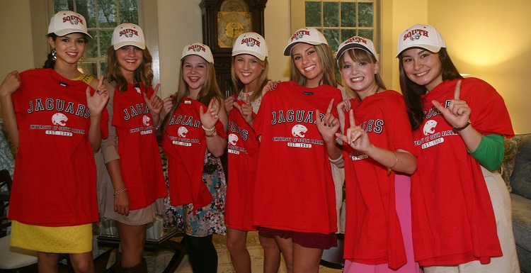 Distinguished Young Women display their University of South Alabama caps while holding up Jaguar T-shirts following a scholarship signing ceremony. They are, from left, Jamie Morelan, Caitlyn Penter, Cassidy Dangler, Kelly Welsh, Tara Principe, Nicole Lusk and Maire Nakada. data-lightbox='featured'