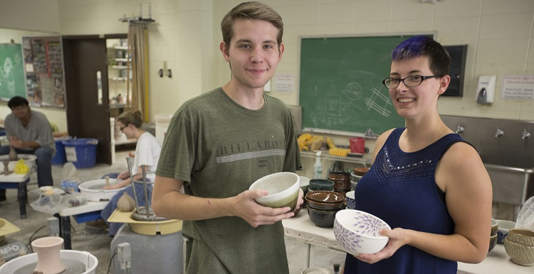 Showing off some of the soup bowls created and donated by USA to benefit Art Soup are Eric Jager, visual arts major, and Alana Kruse, ceramics lab assistant.