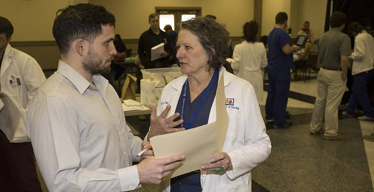 William Crittenden, a fourth-year College of Medicine student, discusses logistics at Project Homeless Connect with Dr. Margaret Moore-Nadler, chair of USA's Health and Wellness Committee and associate professor of community mental health in the College of Nursing at South.