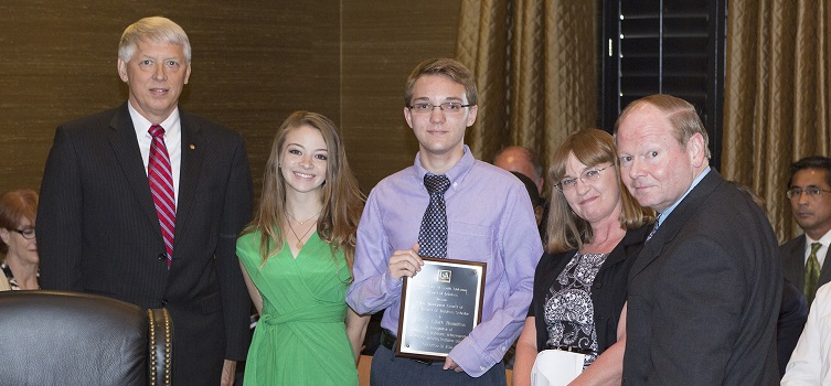 Jeffrey Hamilton, center, was recognized as the first Board of Trustees Scholar at the Board's Sept. 9 meeting. USA President Dr. Tony Waldrop, far left, and Trustee Chair Pro Tempore Dr. Steve Furr, far right, are pictured with Hamilton and members of his family.