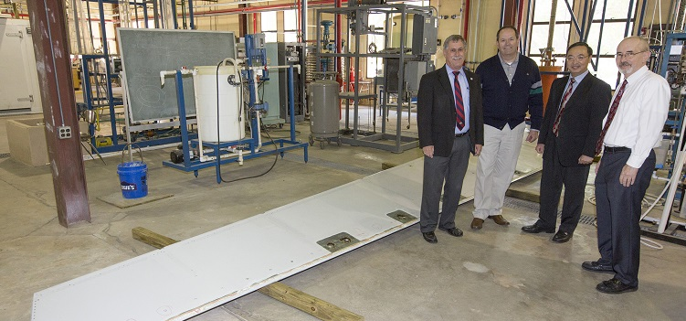 "The donation of an A330 elevator from Airbus to the University of South Alabama will make ""possible for our engineering students to study and test a very large commercial version of the high-strength materials that are the subject of their classes and laboratory experiments,"" said Dr. John Steadman, dean of the College of Engineering. Standing with the elevator, from left, are Steadman; David Trent, Airbus Mobile Engineering Center site director; Dr. Kuang-Ting Hsiao, USA mechanical engineering professor; and David Nelson, chair of mechanical engineering.  data-lightbox='featured'"