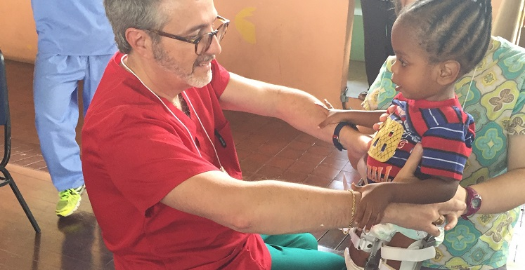 Dr. Dennis Fell, USA chair of physical therapy, helps Kadeon stand with assistance from Jennifer Melancon, a USA physical therapy graduate, during a medical mission trip to Trinidad.