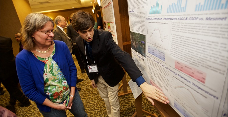 Dr. Sytske Kimball, left, chair of earth sciences, talks with senior meteorology student Nick Grondin about their research project during the 2016 SeCAPS meeting at South.