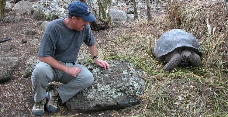 Dr. Stephen J. Walsh watches a Galapagos Island turtle during a visit to the Galapagos Science Center. Walsh is recognized internationally for his studies of human impacts on the islands.