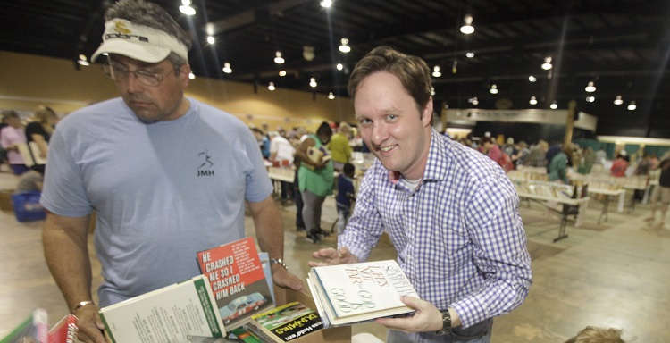 Joshua Cogswell, director of University development, tallies receipts for the Mobile Public Library?s book sale Saturday during the 2015 JaguarsCares National Day of Service.