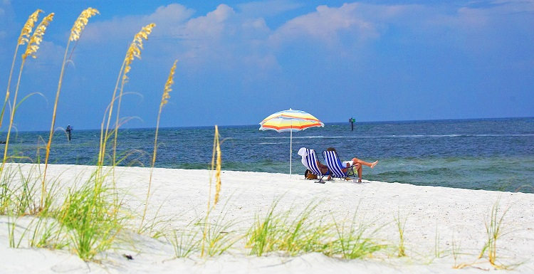 view across sand toward water of the gulf.  Sea Oats in the foreground and umbrella and beach chair in the distance