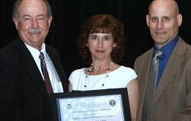 USA officials display the official certification for the School of Computing as a National Center of Academic Excellence during a recent conference in Las Vegas. From left are Dr. Leonard Reinsfelder, deputy director for education and training, National Security Agency; Dr. David Johnson, USA provost and senior vice president for academic affairs; Angela Clark, senior instructor of computing; Dr. Todd Andel, associate professor of computing; Lynne Clark, chief, National Information Assurance Education and Training Program, National Security Agency; and Jacqueline Sullivan, acting program lead, Department of Homeland Security National Cybersecurity Training and Education Program.